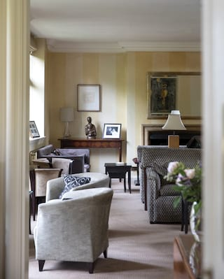 Elegant light-filled lounge with cosy armchairs and antique decorative details