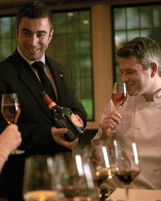 Smiling sommelier showing a wine bottle to two smiling cookery students