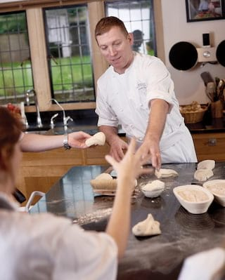 Chef Benoit Blin giving a pastry class to students in a kitchen classroom