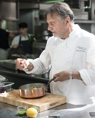 Side-view of Raymond Blanc in chef whites tasting a recipe from a silver spoon