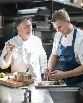 Raymond Blanc smiling as he teaches a fellow chef