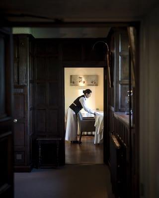 Waitress preparing a table, viewed through a long wood-panelled corridor