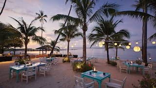 Informal beach restaurant at sunset, surrounded by palms and hanging lanterns
