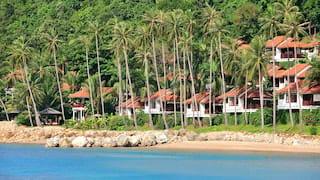 A row of terracotta-tiled beach villas among palms overlooking the beach