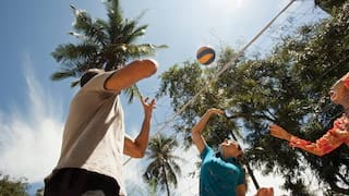 View from underneath a volleyball net of three players reaching for a ball