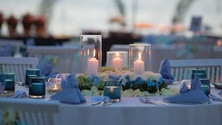 Close-up of a circular table with linen tablecloth, lilac details and candles