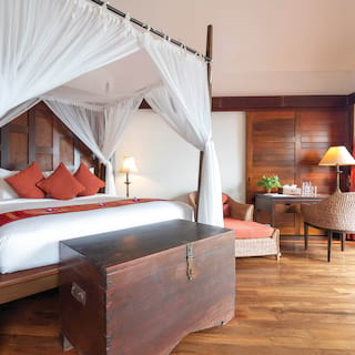 Four-poster hotel bed with wooden chest in front and orange accents