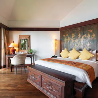 Large pillowy hotel bed with Thai artwork on the wall above