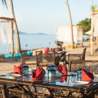 Wicker and bamboo restaurant table on a beach with red and blue accents