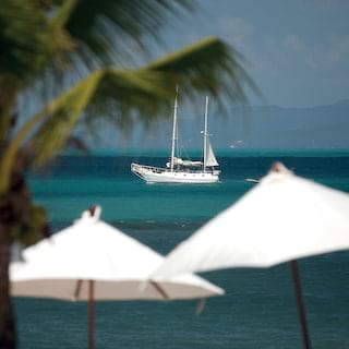 Sailing yacht at sea with white parasols and palms in the foreground