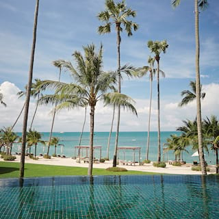 Teal-tiled infinity pool, overlooking gardens and a pristine sandy beach