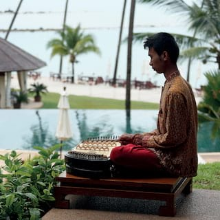 Man playing a traditional Thai 'Khim' instrument overlooking hotel gardens