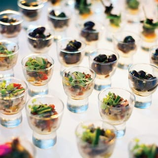 Rows of clear glass egg cups filled with various canapé-style light bites