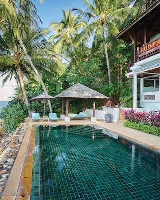 Beachfront villa and emerald-tiled outdoor pool overlooking calm seas
