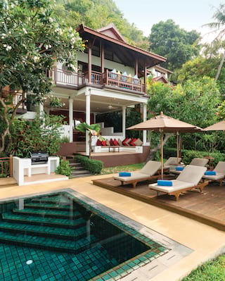 Luxury hotel villa exterior with private pool, sunbeds and lush gardens