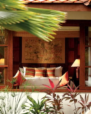 Garden villa exterior with a view of a hotel bed through windows