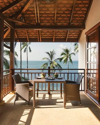 Shaded balcony with rattan seating overlooking the Gulf of Thailand