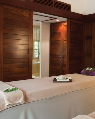 Spa treatment room with teak wood panelled walls and two spa tables