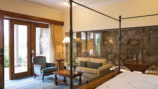 Spacious and light hotel room with glass encased original Inca walls