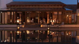 Candlelit restaurant at night with an open terrace reflected in a pool below