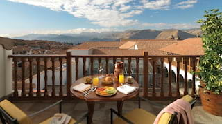 Circular table laden with breakfast dishes on a balcony overlooking Cusco