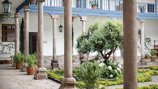 Courtyard lined with stone pillars surrounding ornate gardens