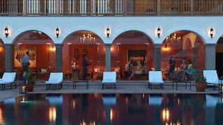 Hotel pool in evening light reflecting the lights of an arched cloister beyond