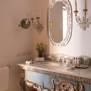 Powder-blue and silver vanity basin below a circular silver framed mirror