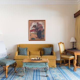 Hotel suite lounge with a blue patterned carpet and mustard coloured sofa