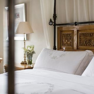 King-size four-poster bed with carved wooden headboard in a bright hotel room