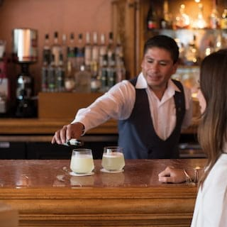 Smiling barman adding pouring two pisco sour cocktails on bar counter