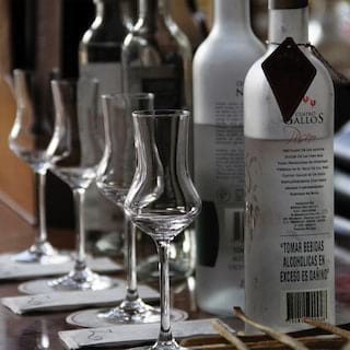 Four pisco glasses in a row with varieties of pisco in the bottle alongside