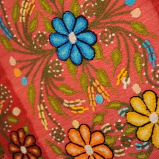 Close-up of vibrant Peruvian fabric with blue and yellow flowers