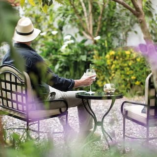Man sitting in a garden chair holding a wine glass, viewed through foliage