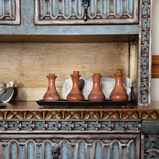 Four clay jars lined on a tray on an intricately carved wooden counter