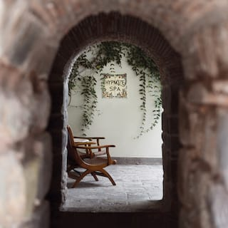 View through an arched stone doorway of two chairs under a sign for Hypnôze Spa