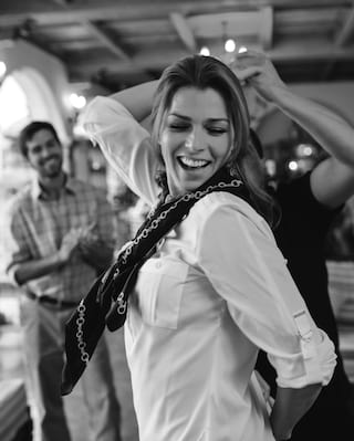 Black and white photo of a lady smiling and dancing