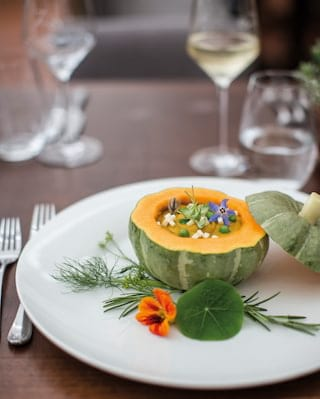 Close-up of white circular plate with pumpkin dish garnished with flowers