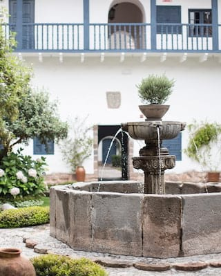 Close-up of a fountain in a courtyard surrounded by a stone path and flower beds
