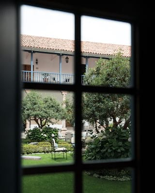 View of an elegant garden courtyard and balcony beyond, through a window