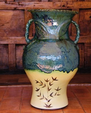 Close-up of a ceramic vase with a shimmering green glaze