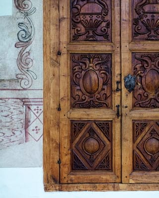 Ornately wooden door with carved panels in a Spanish-colonial style