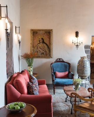 Hotel reception with 16th-century artwork, elegant furnishings and a ceramic pot
