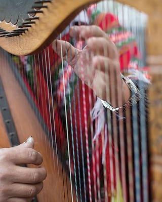 Close-up of two hands playing a wooden carved harp