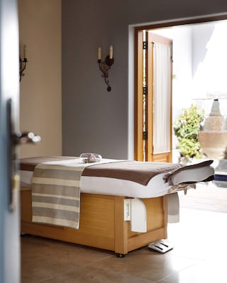 Modern spa treatment room opening onto a private courtyard
