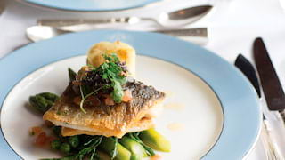 Close-up of sea bass served on a bed of asparagus on a powder-blue rimmed plate