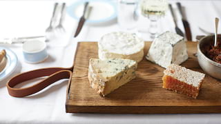 Close-up of a cheese board with wedges of brie, stilton and a fresh cut honeycomb
