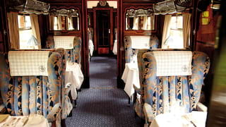 Vintage train carriage with blue liberty print armchair seating and formal dining tables