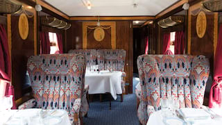 Vintage wood-panelled train carriage with liberty print chairs and formal dining tables