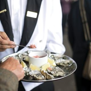 A hand spooning caviar onto ice-chilled oysters with lemon wedges on a silver tray